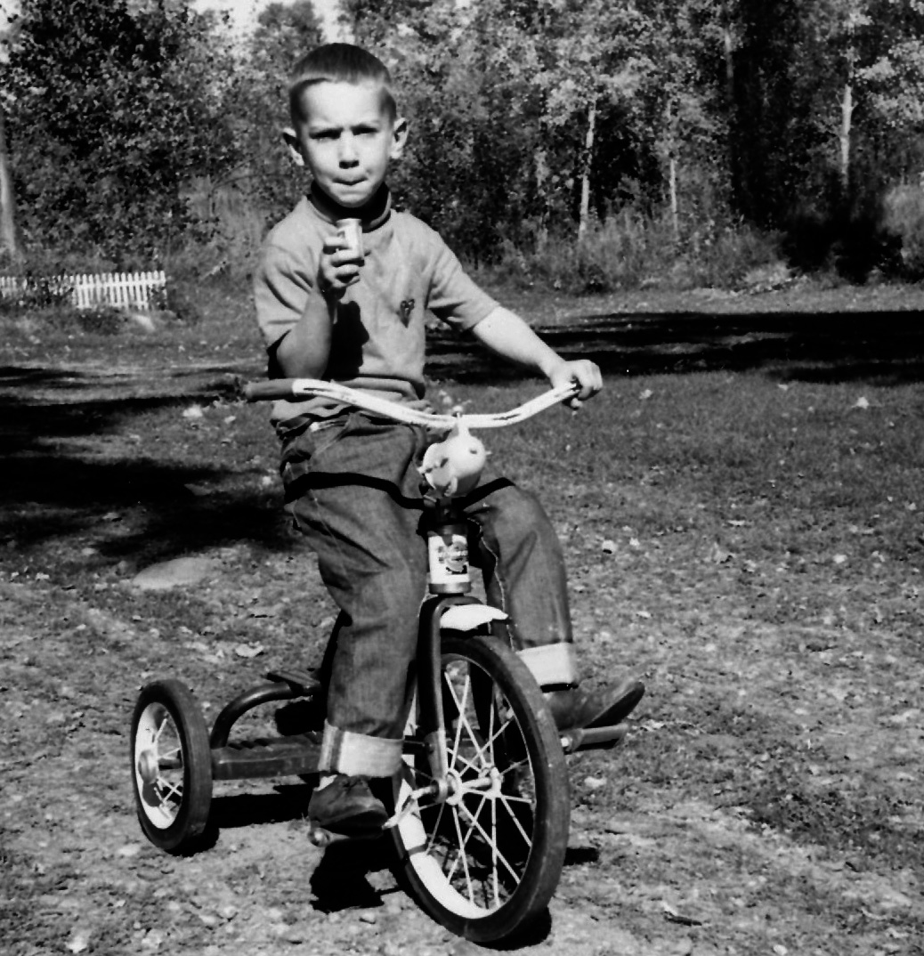 Paul on tricycle in driveway of house in Luck, Wisconsin